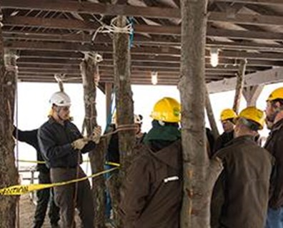 Davey employees from tree service offices, branches and utilities in regions across the U.S. and Canada gather in an indoor forest beneath a pavilion at the Davey Institute for the Davey Institute of Tree Sciences (DITS) program. There they learn tree service techniques and treatment methods.