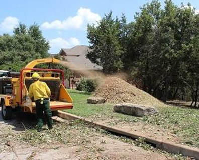 Volunteers from the Lone Star Hand Crew chip materials they removed from local properties to create shaded fuel breaks. These clearances will help prevent the spread of wildfires. | Photo Courtesy: John Durham, Lake Travis Fire Rescue