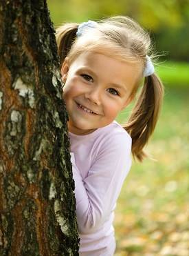 child behind tree trunk