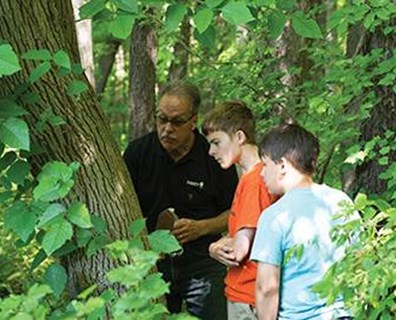 Davey District Manager Gordon Matthews leads the Boy Scout Troop of Stow, Ohio, through a park on an EAB hunt.