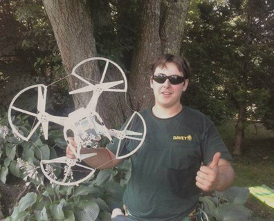 Davey Cape Cod tree services crewmember Reis LeBeau shows off the remote-controlled drone he rescued from a tree.