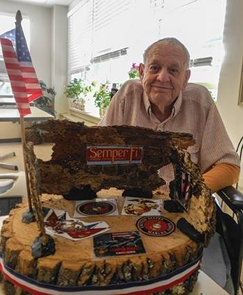Royal Falmouth resident Cal used the wood base Davey's Cape Cod tree services donated to create a monument to his military service in the Marines. Photo credit: Nancy Newman, Royal Falmouth Nursing and Rehabilitation Center.