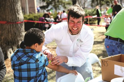 Trimmer Justin Madsen applies a temporary tattoo to a participant of RPU's Arbor Day celebration.