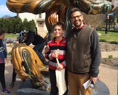 "Dominick, an elementary school student, stands with David Hassler, director of the Wick Poetry Center at Kent State University, after the Kent, Ohio, ""Who's Your Mama"" Earth Day and Environmental Film Festival block party parade. Read why Dominick loves trees in his poem below."