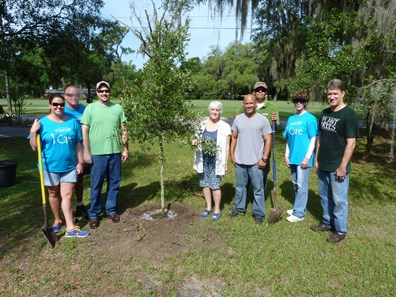 Davey General Foremen Jason Agosto and Daniel Montalvo help plant a tree with other Adopt-a-Tree program volunteers.